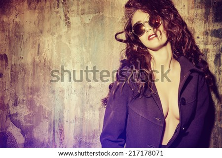 Gorgeous sexual woman alluring by the grunge wall. Fashion, beauty and love concept.