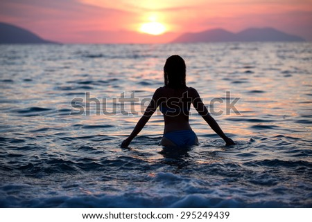 Gorgeous sexy fit woman silhouette swimming in sunset.Free happy woman enjoying sunset. Beautiful woman in water embracing the golden sunshine glow of sunset, enjoying peace, serenity in nature. - stock photo
