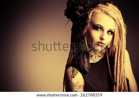 Gorgeous sexy girl with black make-up and long dreadlocks. Gothic style. Fashion. Cosmetics, hairstyle. Tattoo. Vintage, sepia. - stock photo
