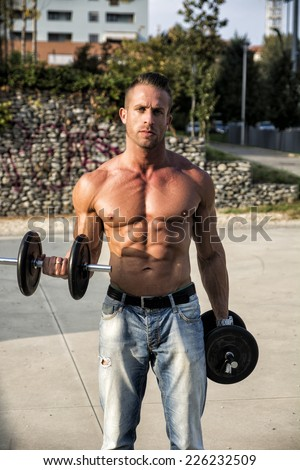 Gorgeous Shirtless Hunk Man Lifting Weights Outdoor. Snowing Healthy Body While Looking at the Camera. - stock photo
