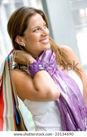 Gorgeous shopping woman holding bags in a shopping mall - stock photo