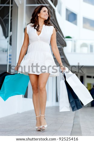 Gorgeous shopping woman walking at the mall holding bags
