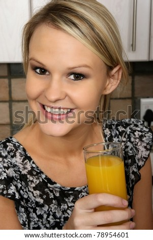 Gorgeous smiling blond girl with a glass of orange juice