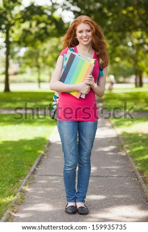 Gorgeous smiling student carrying notebooks on campus at college