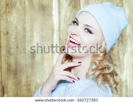 Gorgeous smiling young woman with blond ringlets and blue eyes laughing at the camera over a wooden background with copy space - stock photo
