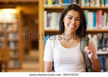 Gorgeous student standing up in a library - stock photo