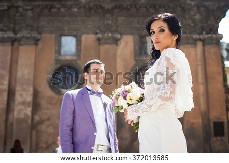 Gorgeous stylish brunette bride and groom posing near old church