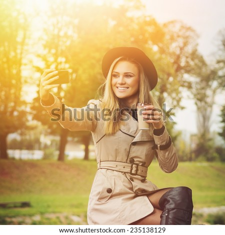 Gorgeous stylish young woman taking a selfie outdoors in autumn. Cute blonde teenage girl in coat, boots and hat sitting in park taking a self portrait with smart phone. - stock photo