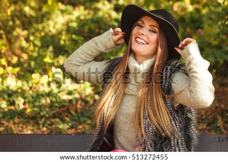 Gorgeous stylish young woman wearing fashionable clothes. Portrait of girl in black hat sitting on bench in park.