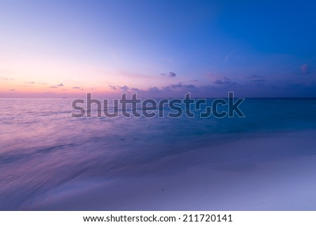 Gorgeous sunset over the ocean. Splash of waves on the white sand beach. Relaxing summer evening. Panorama of tropical island Beach. - stock photo