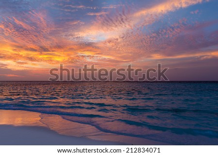 Gorgeous sunset over the ocean. Splash of waves on the white sand beach. Relaxing summer evening. Panorama of tropical sea - stock photo