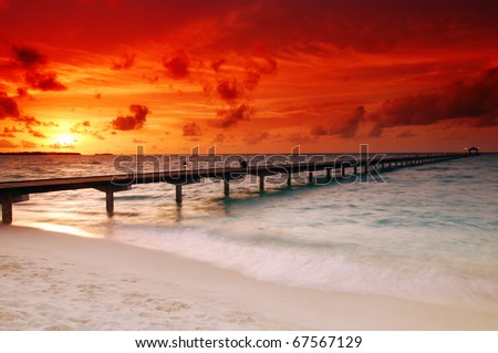 Gorgeous sunset over the sea and a jetty in the tropical paradise of Caribbean - stock photo