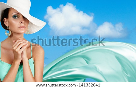 Gorgeous tanned woman over blue sky. Space for text. - stock photo