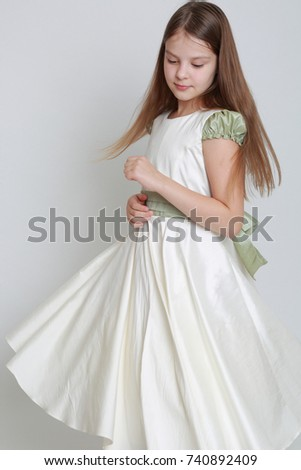 Gorgeous teen girl in a dress posing for a studio portrait