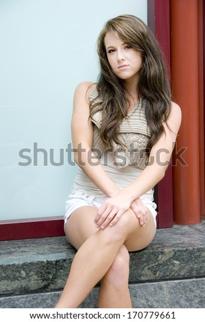 Gorgeous teen model wearing a white top and matching shorts on a sunny day. - stock photo