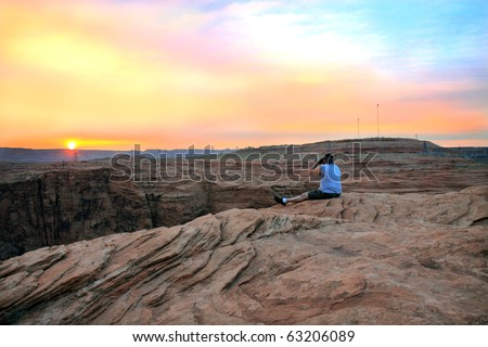 Gorgeous vibrant sunset with vivid colors of orange, yellow, and pink from the top of Glen Canyon, near the dam - stock photo