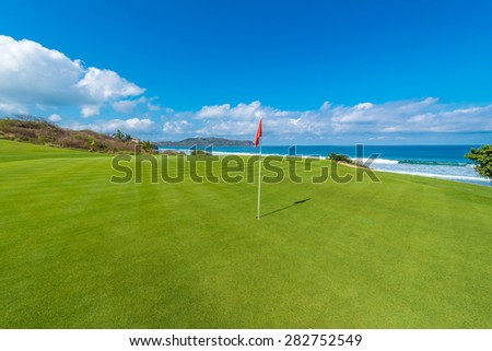 Gorgeous view at the beautiful golf course with sand bunkers and red flag at the ocean side. - stock photo