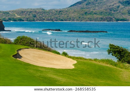 Gorgeous view at the beautiful golf course with sand bunkers at the ocean side. - stock photo