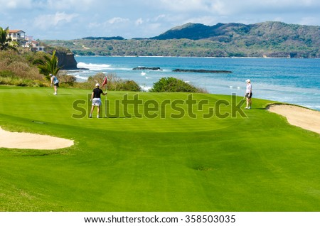 Gorgeous view at the luxury golf course with sand bunkers at the ocean side. - stock photo