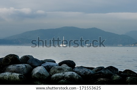 Gorgeous view at the marine scenery. A boat, ship, vessel moves across the ocean inlet with the rocky beach and the mountains and hills as a great background. Vancouver, Canada. - stock photo