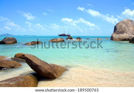 gorgeous view from the beach over the turqouise ocean with a old ship at the background - stock photo