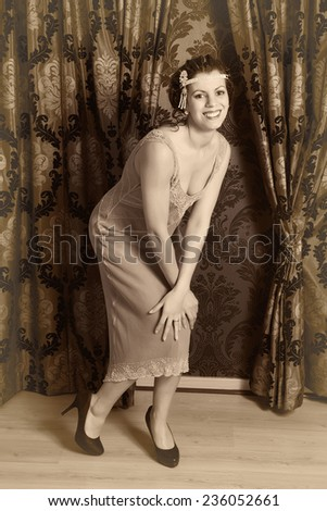 Gorgeous vintage 1920s lady dancing the charleston in a flapper dress with headband - stock photo