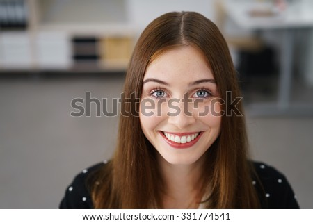 Gorgeous vivacious young woman with a beaming smile and happy eyes smiling directly at the camera, close up head and shoulders portrait indoors - stock photo