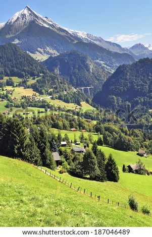 Gorgeous weather in the vicinity of  ski resort of Leysin in the Swiss Alps. The picturesque alpine meadows, rural houses chalets. Away bridges across the abyss and the majestic snow-capped mountains - stock photo