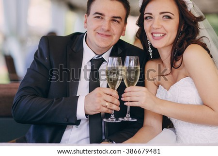 gorgeous wedding couple enjoys champagne sitting in the restaurant