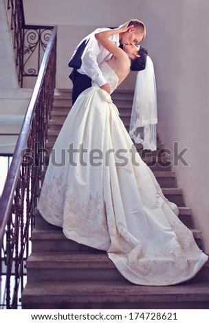 gorgeous wedding couple kisses on stairs - stock photo