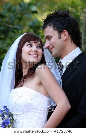 Gorgeous wedding couple smiling and looking at each other