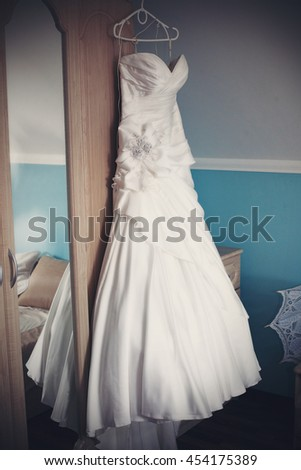 Gorgeous wedding dress hangs from the wardrobe behind a mirror
