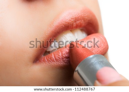 Gorgeous woman applying lipstick