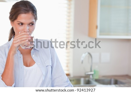 Gorgeous woman drinking a glass of water in her kitchen - stock photo
