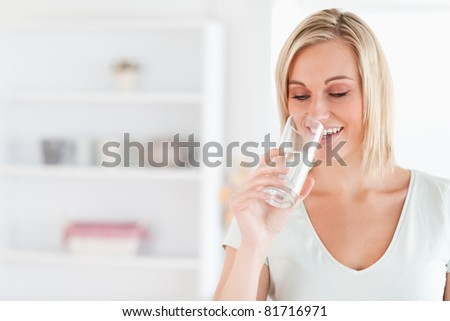 Gorgeous woman drinking water in her kitchen - stock photo