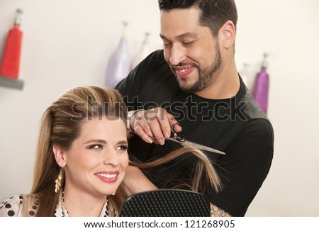 Gorgeous woman getting haircut by attractive Arab hairdresser - stock photo
