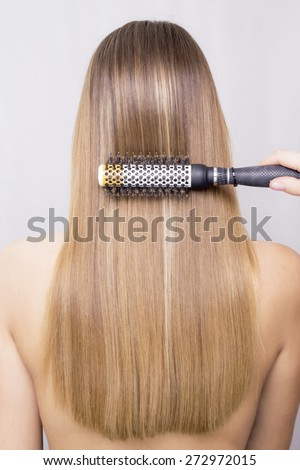 Gorgeous woman hair from behind with a hair brush in it