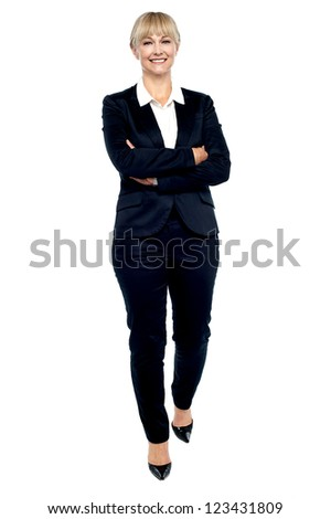 Gorgeous woman in business suit walking towards you, hands crossed. - stock photo