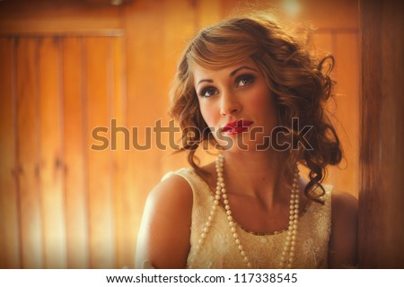 Gorgeous woman in flapper dress standing  in a train carriage - stock photo