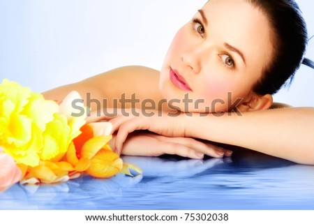 Gorgeous woman lying on blue water surface and looking at camera - stock photo