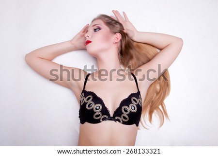 Gorgeous woman lying on grey background  and posing sexy. Studio shooting. Sexuality and sensuality. - stock photo