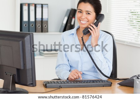 Gorgeous woman on the phone while typing on a keyboard at the office - stock photo
