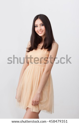 Gorgeous woman. Portrait of beautiful smiling young woman standing in cute beige dress isolated on gray background. Sexy mixed race Chinese Asian Caucasian female model. - stock photo
