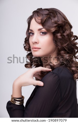 Gorgeous woman professional make up and hairstyle on grey background. Studio shooting