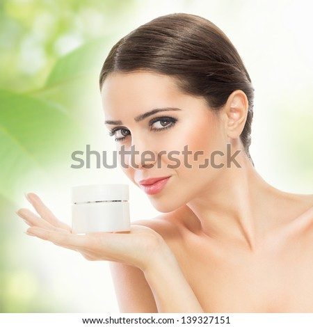 Gorgeous woman smiling and holding face cream - stock photo