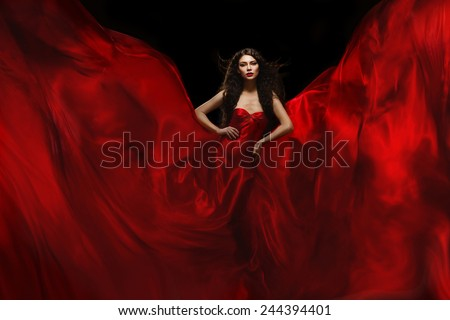 Gorgeous woman standing in red flying atlas flames over black background