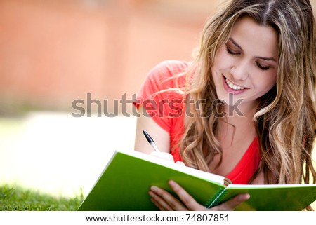 Gorgeous woman studying outdoors lying on the floor - stock photo