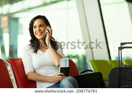 gorgeous woman talking on mobile phone at airport - stock photo