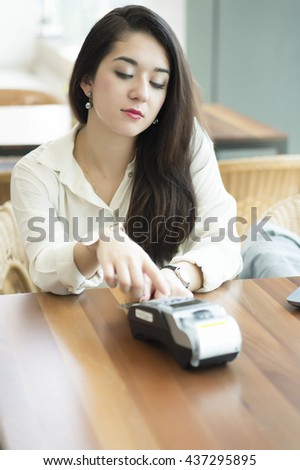 Gorgeous woman using credit card reader machine at the cafe - stock photo