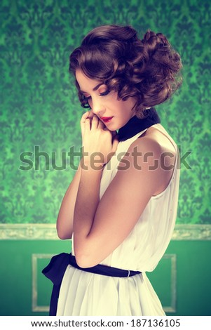 Gorgeous woman vintage toned image in retro room. Professional make up and hairstyle. Studio lighting - stock photo